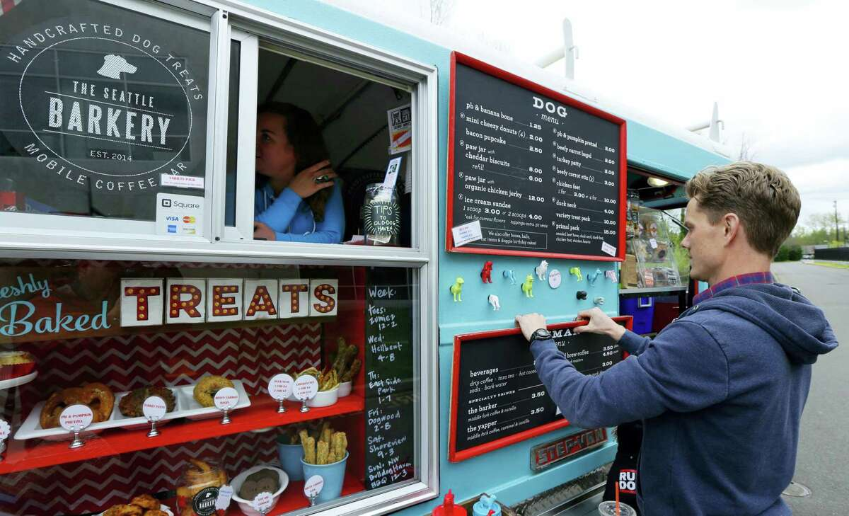 Ben Ford, right, co-owner of the the Seattle Barkery, a food truck specializing in treats for dogs, adjusts menus for both dogs and humans, while co-owner wife Dawn waits in the window for customers during the lunch hour, at the headquarters for the clothing and skateboard retailer Zumiez, in Lynnwood, Wash.