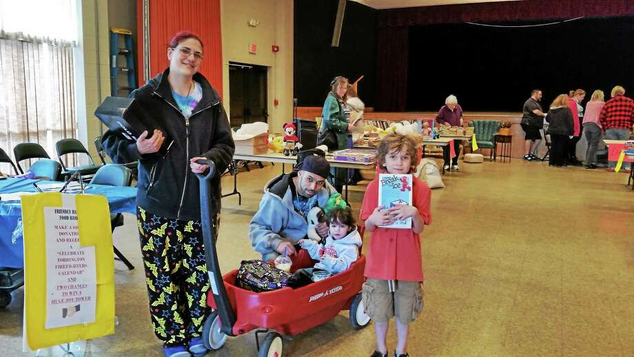 Michelle Franklin-Aponte of Torrington; husband Ramon of Waterbury; daughter Ayriana, 2; and son Mark, 4, at Torrington's third annual Community Tag Sale recently. Photo: N.F. Ambery — Special To The Register Citizen