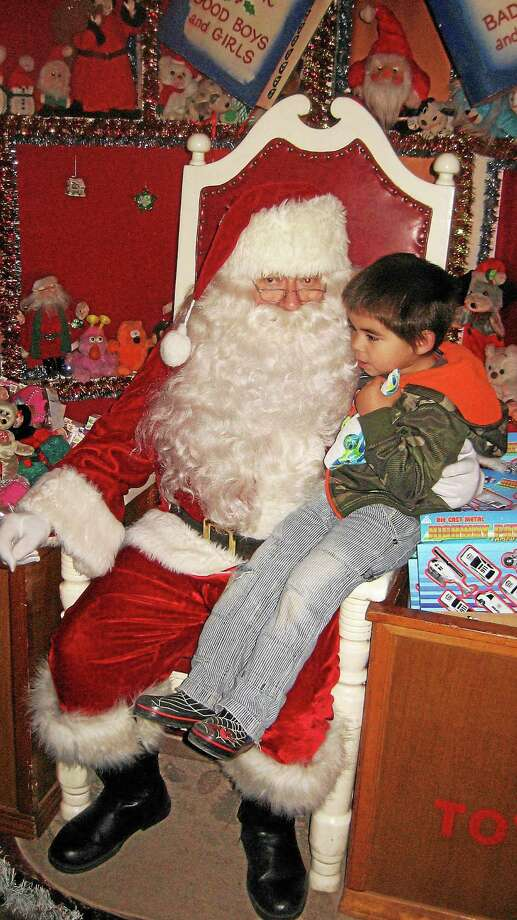 Photo by John TorsielloA child tells Santa his Christmas wishes during the opening of Christmas Village Dec. 6. The village will be open until Dec. 24. Photo: Journal Register Co.