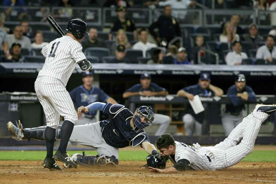 Jacoby Ellsbury slides under the tag of Rays catcher Curt Casali to steal home as Brett Gardner steps out of the way during the fifth inning on Friday. Photo: Julie Jacobson — The Associated Press  / Copyright 2016 The Associated Press. All rights reserved. This material may not be published, broadcast, rewritten or redistributed without permission.