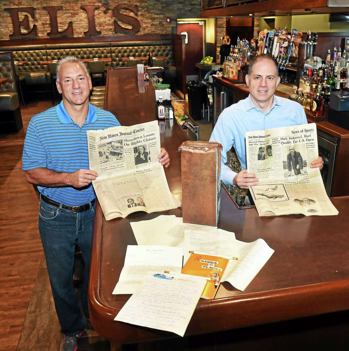 (Peter Hvizdak - New Haven Register) Richard Ciardiello, owner of the Eli's restaurant chain in the New Haven area, left, and Shawn Reilly, Eli's Director of Operations, at the Eli's restaurant in Orange with 1964 artifacts found in a time capsule found on the construction site of the Orange restaurant when it was being built recently.