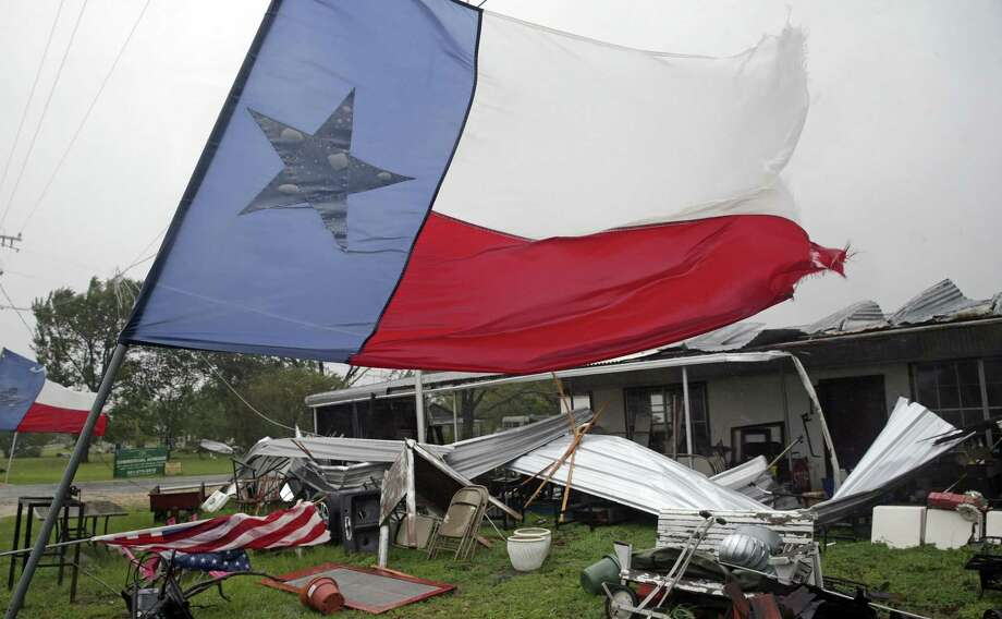 Texas flags remain in front of a highway 183 business which had been ripped up by high winds as Hurricane Harvey hits the countryside east of San Antonio on August 26, 2017. Photo: Tom Reel, Staff / San Antonio Express-News / 2017 SAN ANTONIO EXPRESS-NEWS