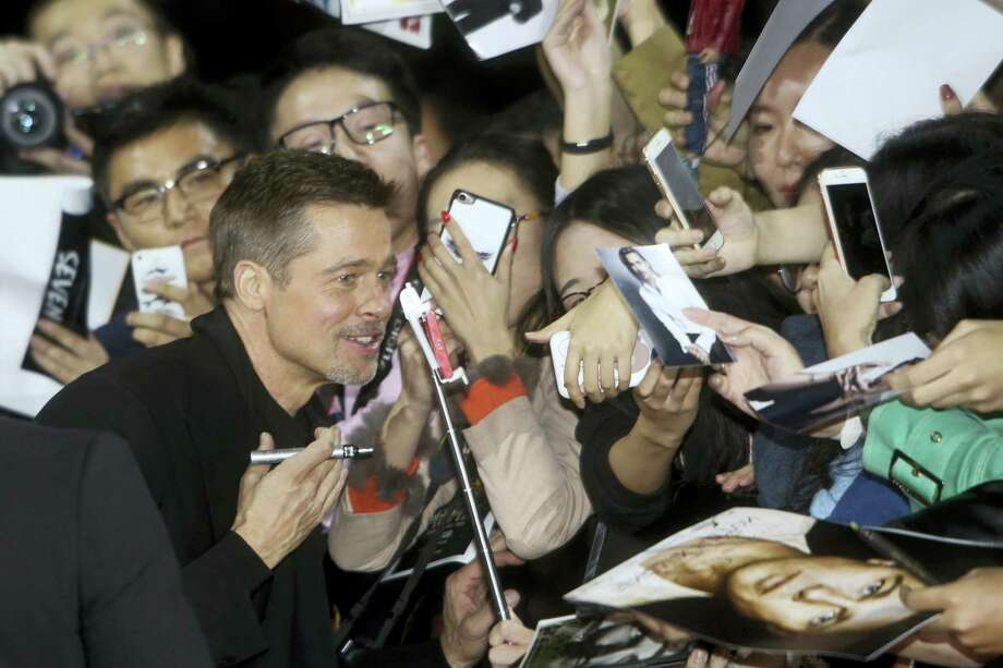 Actor Brad Pitt poses for photos with Chinese fans as he arrives at a premiere of director Robert Zemeckis' new film 'Allied' in Shanghai, China on Nov. 14, 2016. Brad Pitt made his first promotional appearance for a movie in China since reportedly being banned over a film about Tibet almost 20 years ago. Photo: Color China Photo Via AP  / COLOR CHINA PHOTO