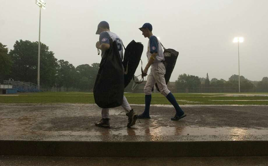 Stamford_072206_After their game against Ridgefield was rained out in the top of the third inning, two Norwalk Babe Ruth 15 year-olds leave the dugout with their equipment. Officials said the game will resume at 10:00 a.m. Sunday. Andrew Sullivan/Staff photo Staff Photo Andrew Sullivan Photo: Andrew Sullivan / ST / 00000088A