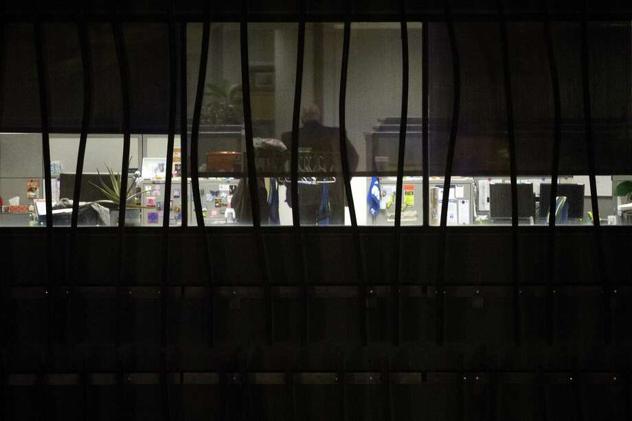 A person is seen in a building on the U.S. Census  Bureau headquarters campus as police search for an armed man who, according to a fire official, shot a security guard at a gate to the facility in Suitland, Md., Thursday, April 9, 2015. (AP Photo/Cliff Owen) Photo: AP / FR170079 AP