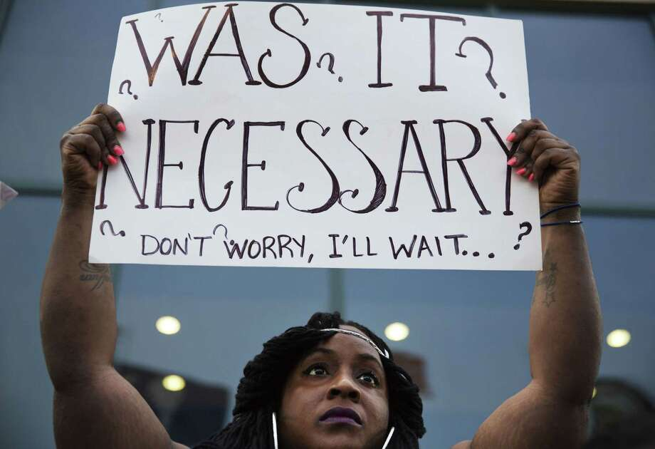 Laquanda Multrie, of Charleston, S.C., holds a sign during a rally in North Charleston, S.C. on Friday, April 10, 2015 protesting the fatal police shooting of Walter Scott. Scott was killed by a police officer after a traffic stop on Saturday. Officer Michael Slager has been fired and charged with murder. (AP Photo/David Goldman) Photo: AP / AP