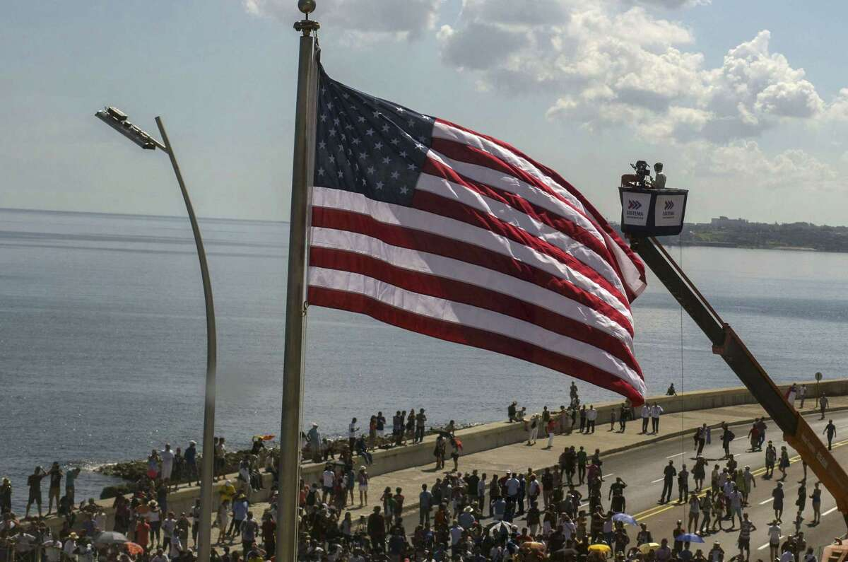 In this photo taken through a window, Cuban videographers film the U.S. flag from a crane after it was raised at the U.S. Embassy in Havana, Friday, Aug. 14, 2015. The Stars and Stripes rose over the newly reopened U.S. Embassy after a half-century of broken diplomatic relations.