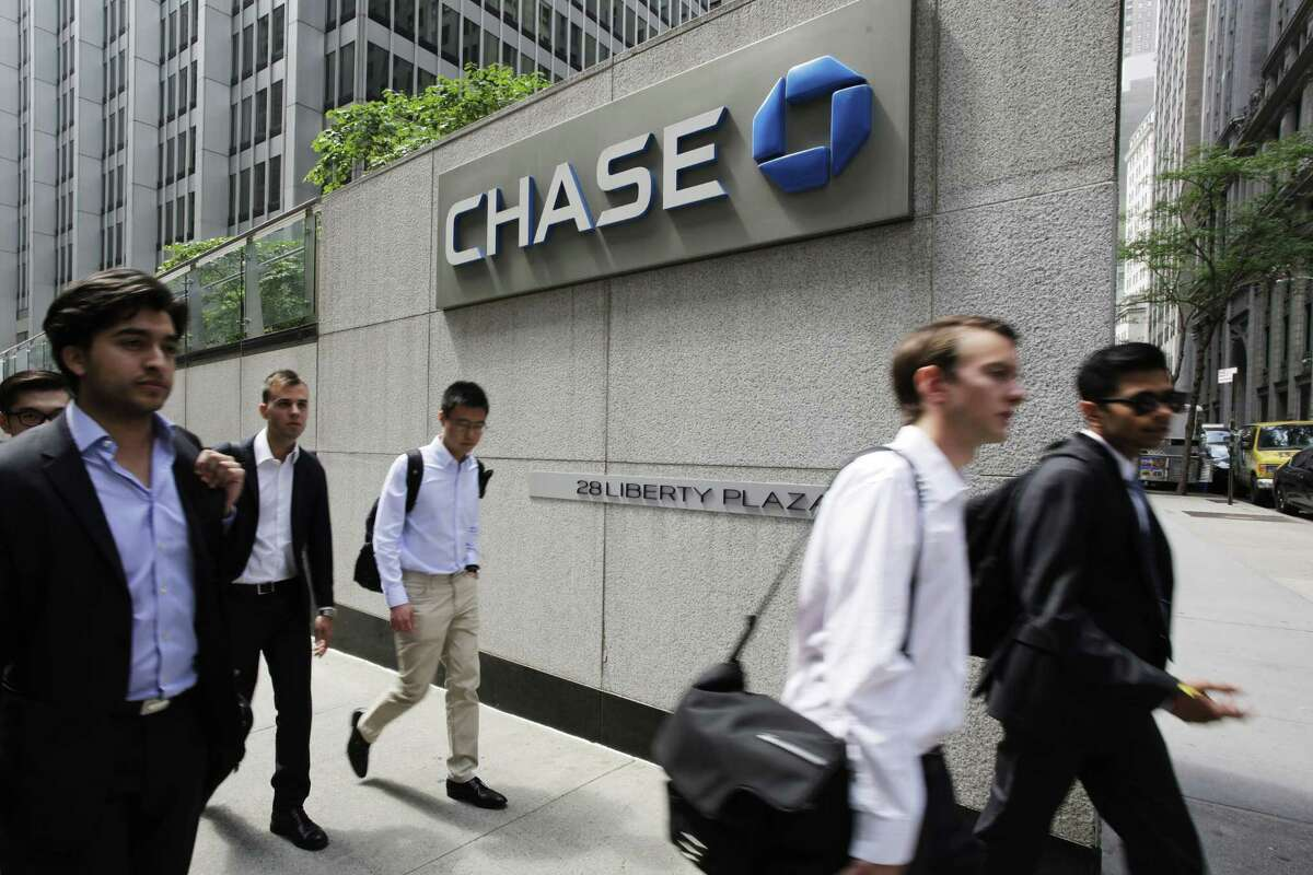 In this Monday, July 13, 2015 photo, pedestrians pass a Chase Bank office tower in New York's financial center. Federal regulators on Monday, July 20, 2015 are directing the eight biggest U.S. banks to hold capital at levels above industry requirements, to cushion against unexpected losses and reduce the chances of future taxpayer bailouts. JPMorgan Chase is the only one that doesn't already meet the requirements.