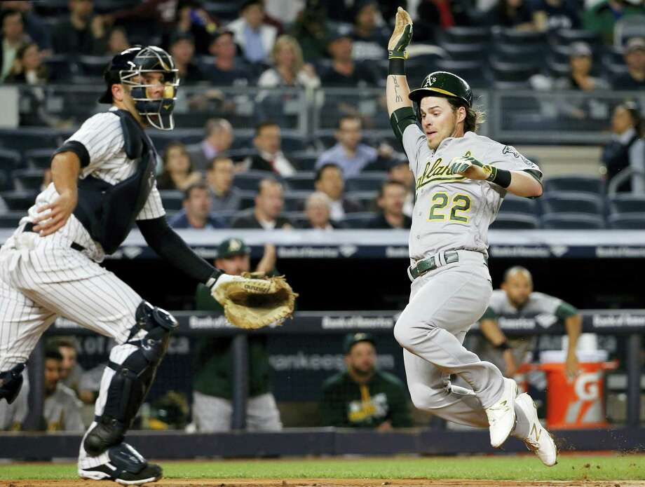 New York Yankees catcher Brian McCann (34) waits for a throw as Oakland Athletics' Josh Reddick (22) scores on Jed Lowrie's fourth-inning single Thursday in New York. The Athletics swept the Yankees. Photo: KATHY WILLENS — THE ASSOCIATED PRESS  / Copyright 2016 The Associated Press. All rights reserved. This material may not be published, broadcast, rewritten or redistributed without permission.