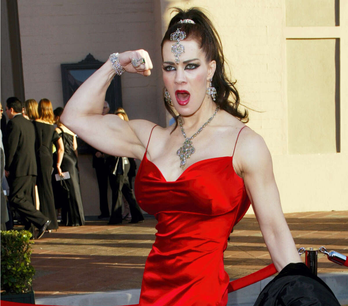 In this Nov. 16, 2003, file photo, Joanie Laurer, former pro wrestler known as Chyna, flexes her bicep as she arrives at the 31st annual American Music Awards, in Los Angeles. Chyna, the WWE star who became one of the best known and most popular female professional wrestlers in history in the late 1990s, has died at age 45. Los Angeles County coroner's Lt. Larry Dietz says Chyna, whose real name is Joan Marie Laurer, was found dead in Redondo Beach on Wednesday, April 20, 2016.