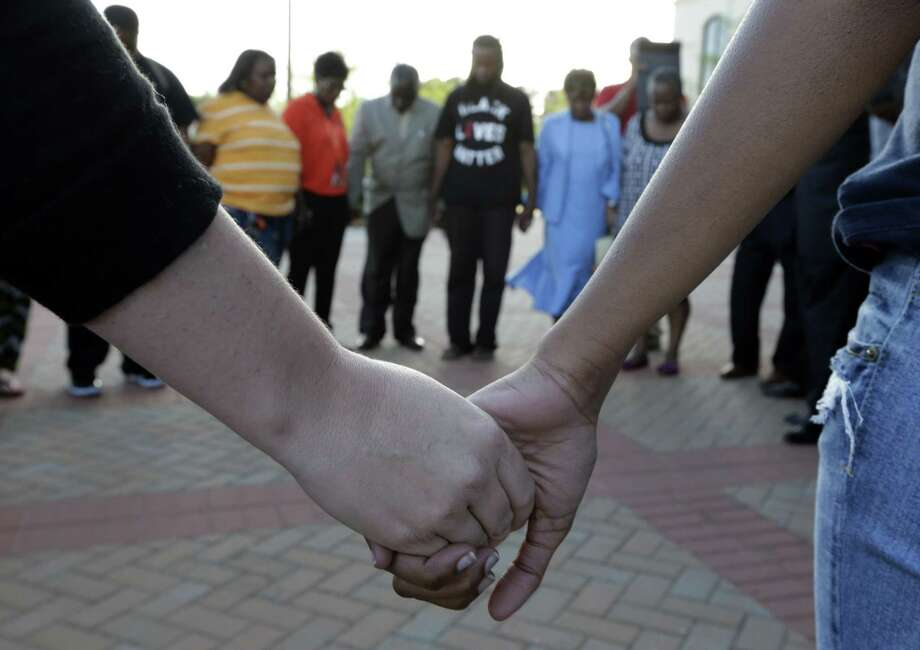 People hold hands in prayer during a rally for the killing of Walter Scott by a North Charleston police officer Saturday, after a traffic stop in North Charleston, S.C., Thursday, April 9, 2015. The officer, Michael Thomas Slager, has been fired and charged with murder. (AP Photo/Chuck Burton) Photo: AP / AP