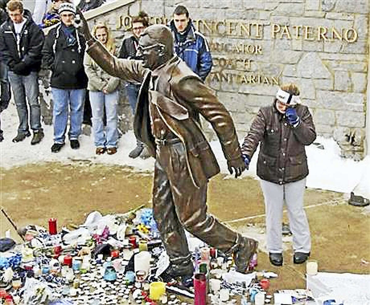 In this Jan. 22, 2012, file photo, a woman pays her respects at a statue of former Penn State football coach Joe Paterno outside Beaver Stadium on the Penn State University campus in State College, Pa. More than 200 former Penn State football players are petitioning university leaders to return the bronze statue of Paterno that stood outside the school's football stadium. The statue of the late football coach was removed in 2012. The players sent a letter Tuesday, July 5, 2016, to the board of trustees and Penn State President Eric Barron calling for the statue's return.