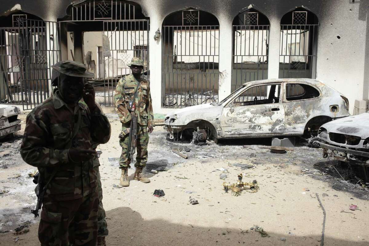 In this photo taken Wednesday, April 8, 2015, Nigerian soldiers stand guard in front of the burned out palace of the Emir of Gwoza, in Gwoza, Nigeria, a town newly liberated from Boko Haram. Each day brings new reports of atrocities, with mass graves being discovered in towns seized back from the militants who had set up a so-called ìIslamic caliphateî across a great swath of northeast Nigeria. Boko Haram's nearly 6-year-old Islamic uprising in northeast Nigeria that has killed thousands ó a reported 10,000 just last year ó and forced more than 1.5 million from their homes.