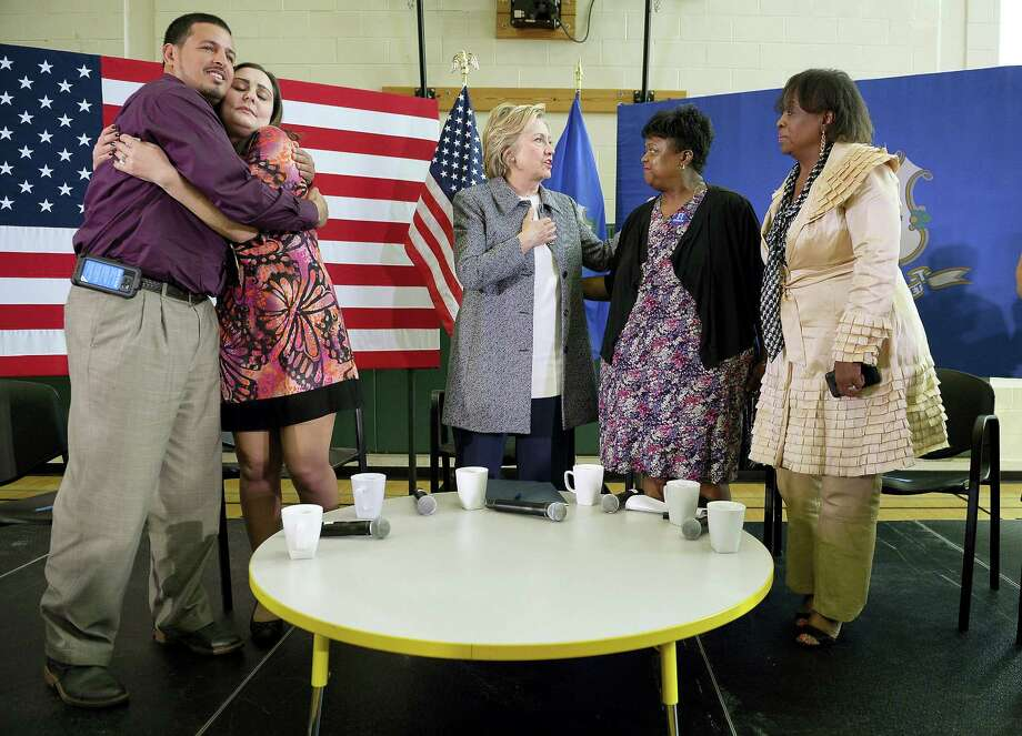 Democratic presidential candidate Hillary Clinton, center, speaks to Kim Washington, second from right, during a campaign event, Thursday in Hartford. Clinton stopped in Hartford for a discussion on gun violence prevention with family members of gun violence victims. Iran Nazario, left, hugs Erica Smegielski, whose mother was principal of Sandy Hook Elementary School and was killed in the December 2012 shooting at the school in Newtown, Conn. At right is Deborah Davis who lost her 20-year-old son, Phillip, to gun violence in 2010. Photo: (AP Photo/Jessica Hill) / FR125654 AP