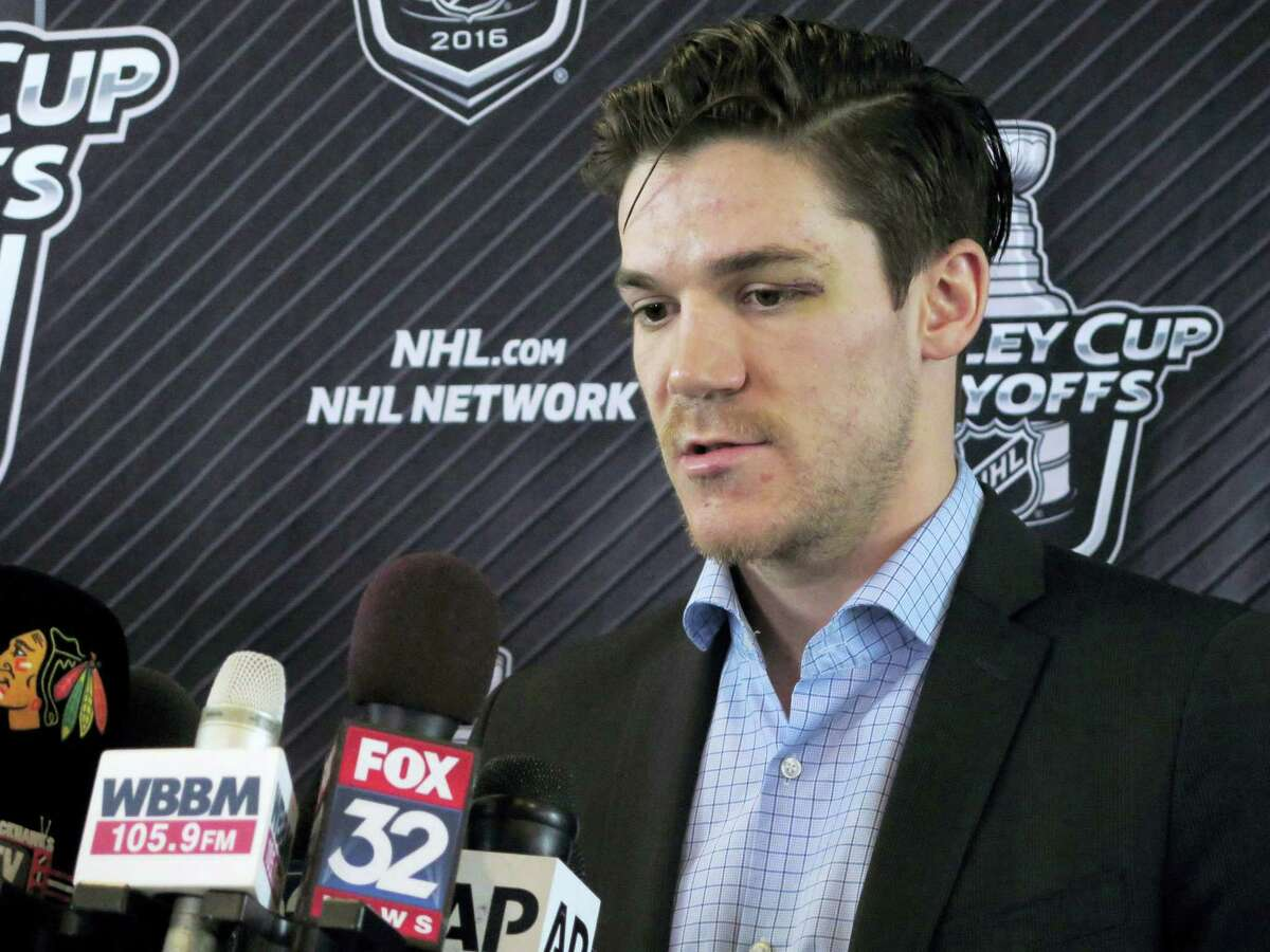 Blackhawks forward Andrew Shaw talks to reporters before the team left for St. Louis on Wednesday at Chicago's O'Hare International Airport.