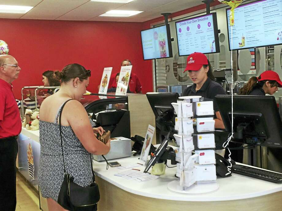 A customer pays for her fresh fruit smoothie Wednesday at the new Edible To Go store in Wallingford, in the Edible Arrangements headquarters. Photo: LUTHER TURMELLE — NEW HAVEN REGISTER