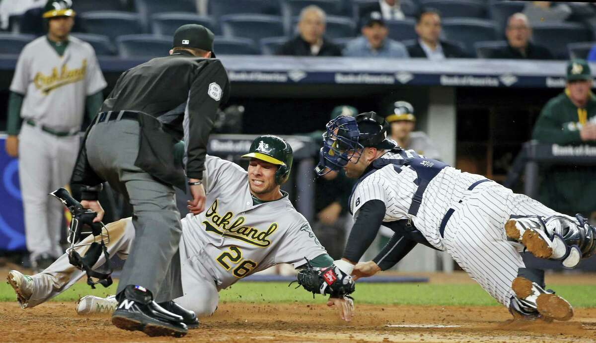 Home plate umpire Jeff Kellogg watches as the Athletics' Danny Valencia (26) is tagged out at the plate by Yankees catcher Brian McCann on Wednesday.