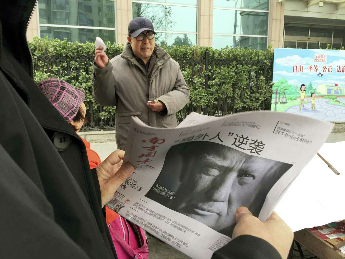 """A Chinese man holds up a Chinese newspaper with the front page photo of U.S. President-elect Donald Trump and the headline """"Outsider counter attack"""" at a newsstand in Beijing, China, Thursday."""
