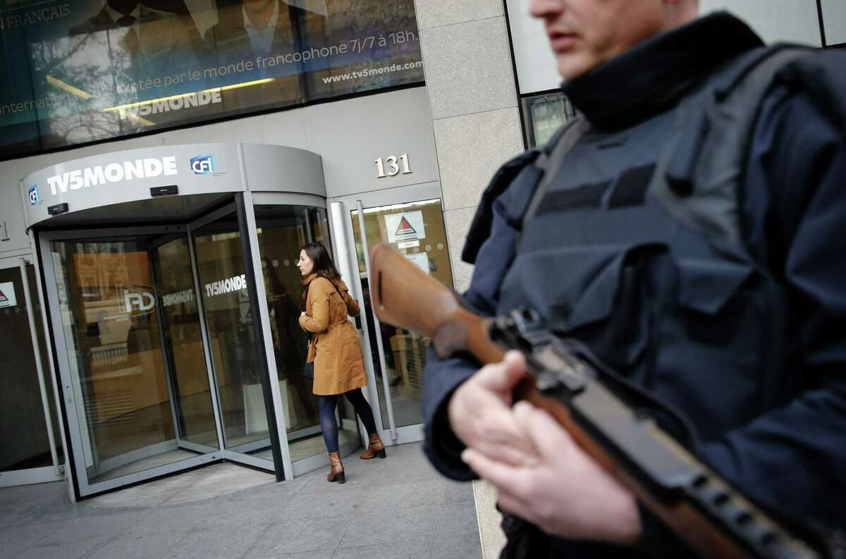 A policeman stands guard in front of TV5 Monde headquarters in Paris, France, Thursday April 9, 2015. A French television network has been hacked by people claiming allegiance to the Islamic State group, the channel's director said Thursday. The hackers briefly cut transmission of 11 channels belonging to TV5 Monde and took over its websites and social media accounts. (AP Photo/Christophe Ena)