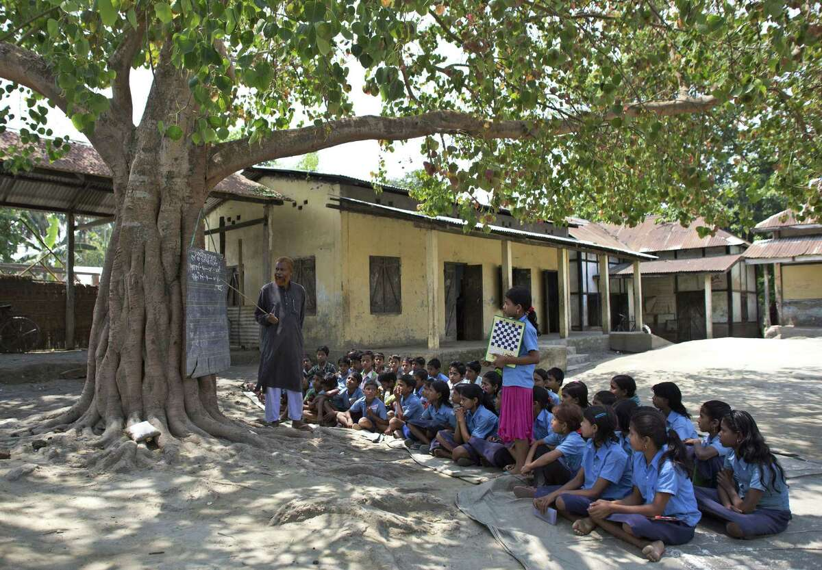Indian school children attend a class under a tree outside a school in east Gagolmari village about 70 kilometers (44 miles) east of Gauhati, India, Thursday, April 9, 2015. According to the UNESCO Education for All Global Monitoring Report 2015, only half of all countries have achieved the most watched goal of universal primary enrollment. The report launched Thursday says, India has reduced its out of school children by over 90% Since 2000.
