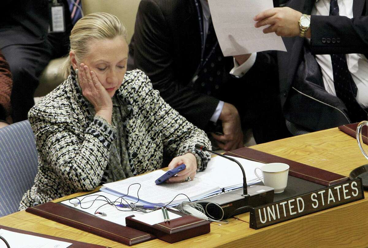 In this March 12, 2012, file photo, then-Secretary of State Hillary Rodham Clinton checks her mobile phone after her address to the Security Council at United Nations headquarters. An impromptu meeting between Bill Clinton and the nation's top cop could further undermine Hillary Clinton'Äôs efforts to convince voters to place their trust in her, highlighting perhaps her biggest vulnerability.