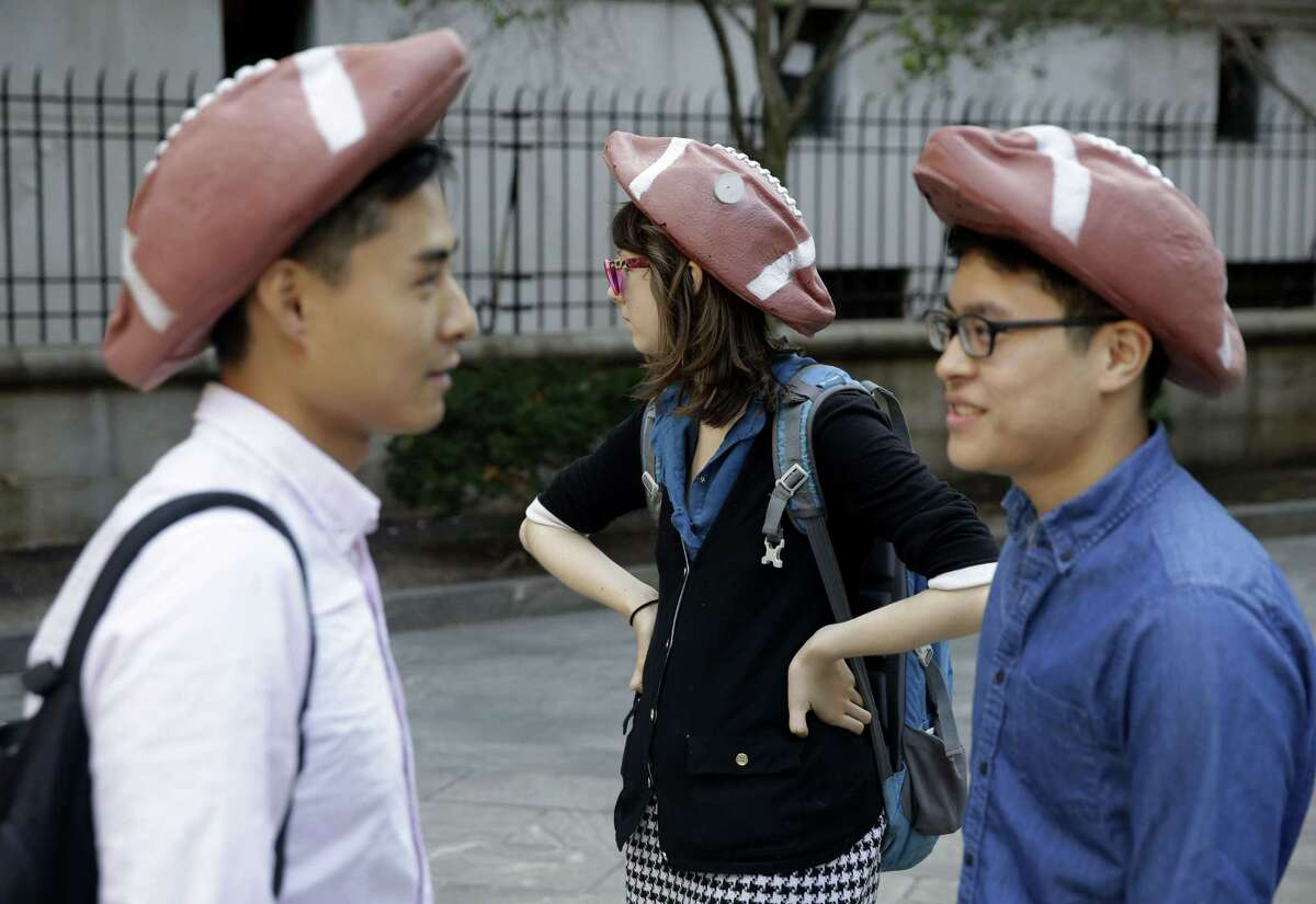 People wearing hats in the shape of deflated footballs gather Wednesday outside a federal courthouse in New York.