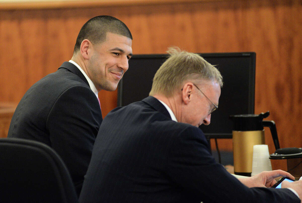Former New England Patriots football player Aaron Hernandez smiles with defense attorney Charles Rankin in the courtroom of the Bristol County Superior Court House in Fall River, Mass., Wednesday, April 8, 2015. The fate of Hernandez is now in the hands of a jury, which began its first full day of deliberations Wednesday in his murder trial. Hernandez is charged with the June 2013 shooting death of Odin Lloyd. (AP Photo/Faith Ninivaggi, Pool)