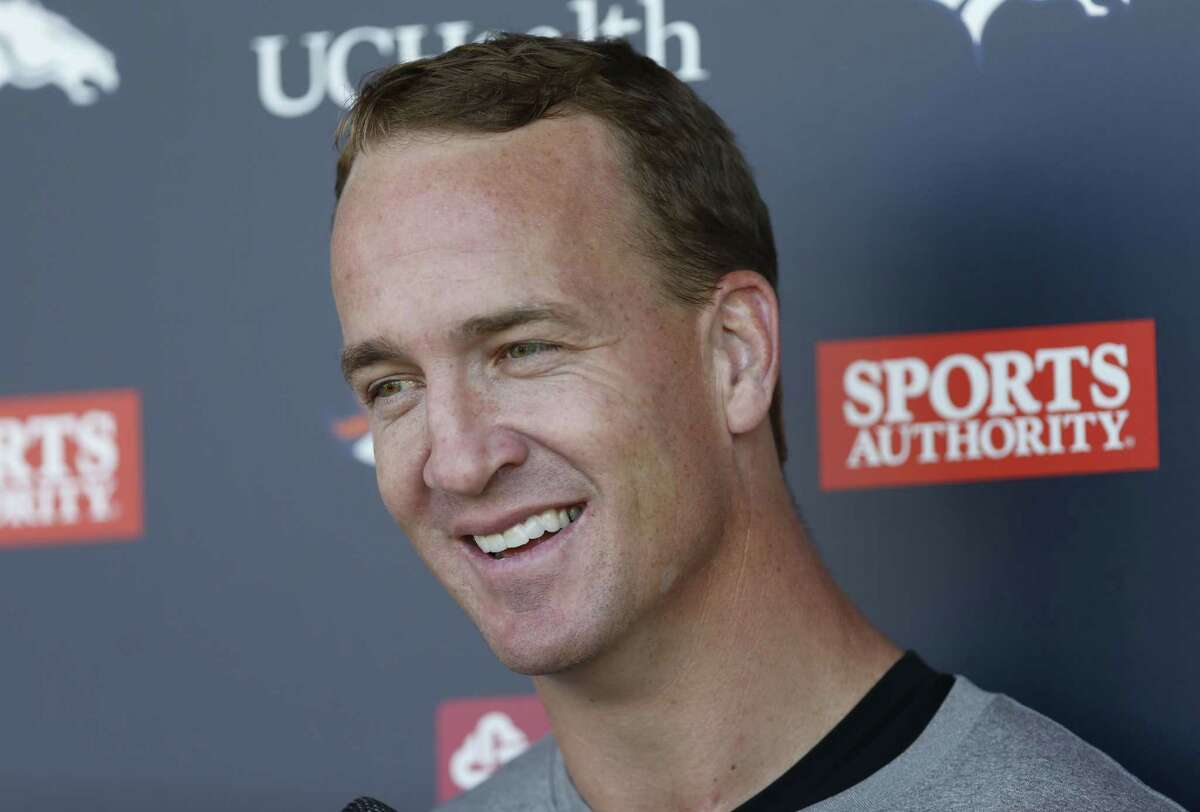 Denver Broncos quarterback Peyton Manning jokes with reporters after the morning session at the team's training camp Wednesday in Englewood, Colo.
