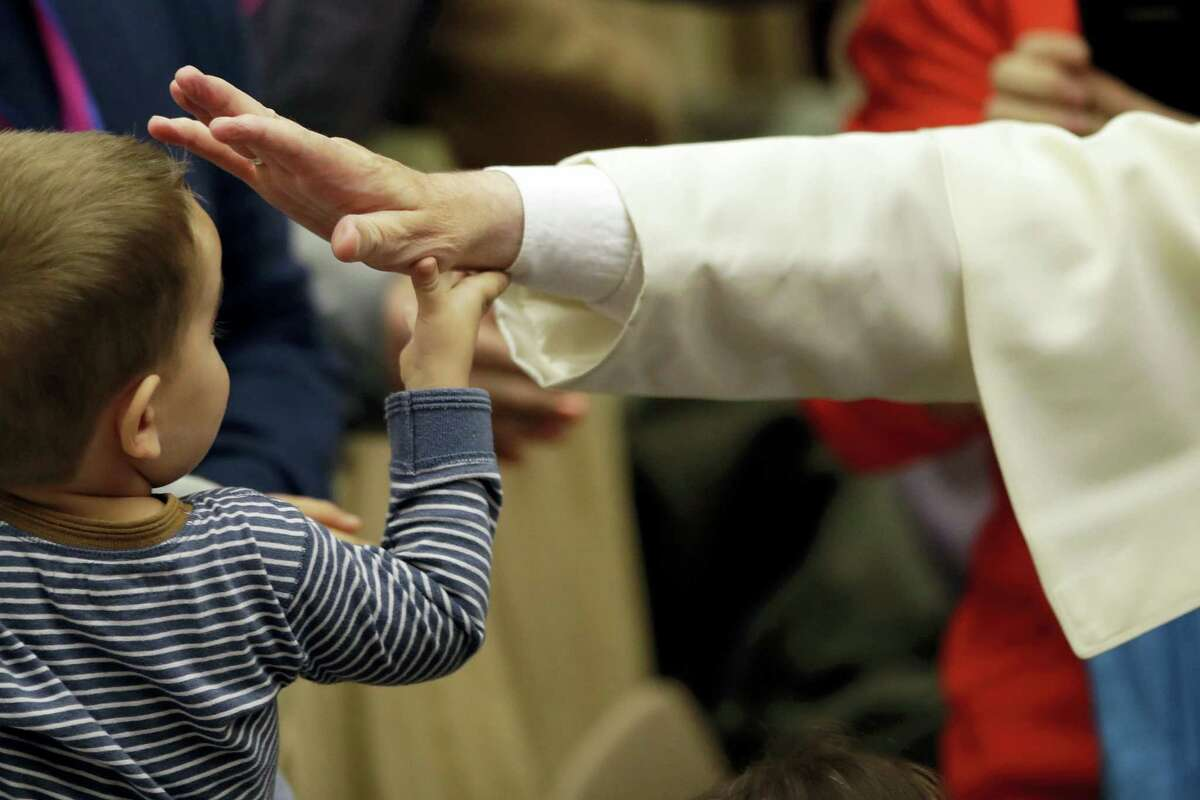 Pope Francis blesses a child during an audience with the participants of homeless jubilee in the Paul VI Hall at the Vatican, Friday, Nov. 11, 2016.