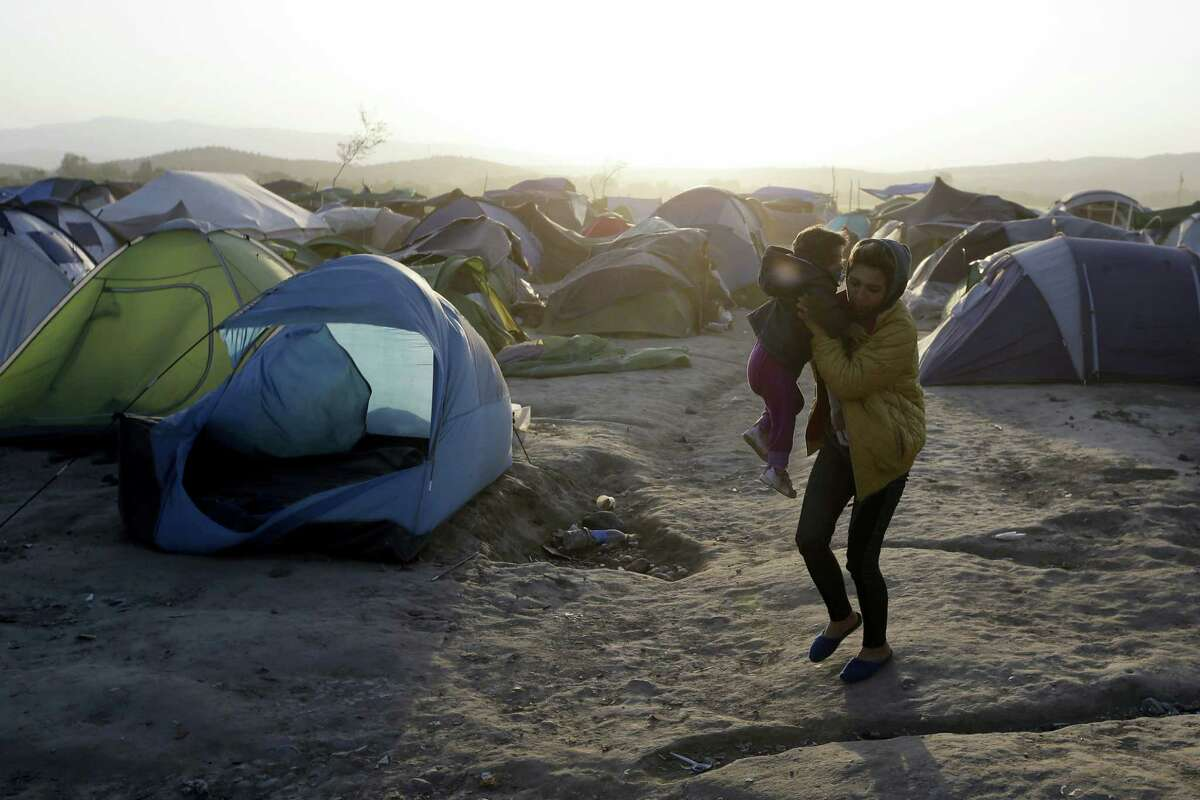 """A woman holds her baby as she walks by a tent blown by a strong wind at a camp for migrants and refugees at the northern Greek border point of Idomeni, Greece, Wednesday, April 20, 2016. Human Rights Watch says the initial round of deportations of migrants from Greece to Turkey under a new European Union-Turkey deal were """"rushed, chaotic and violated the rights of those deported."""""""