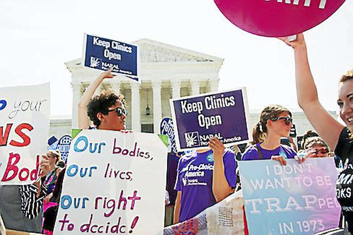A pro-choice activist holds a Planned Parenthood sign while awaiting the Supreme Court's ruling on abortion access in front of the Supreme Court in Washington on June 27.