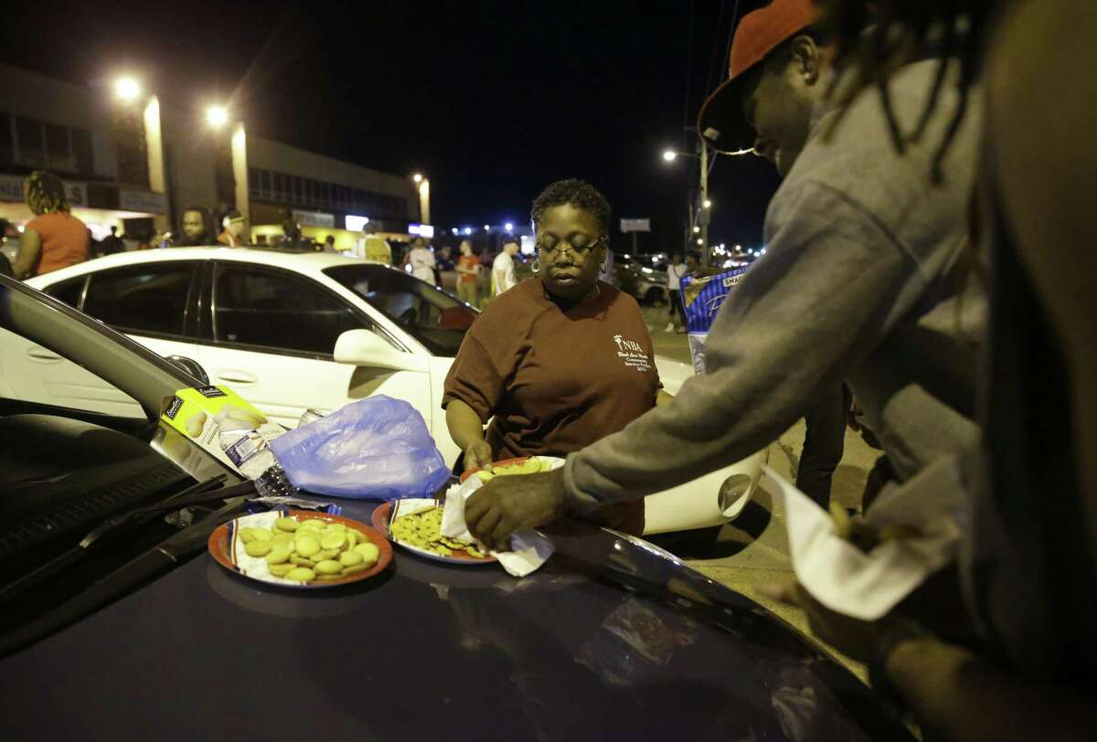 """Cat Daniels puts out snacks as a smaller group of protesters gathers along West Florissant Avenue in Ferguson, Mo., Tuesday, Aug. 11, 2015. The St. Louis suburb has seen demonstrations for days marking the anniversary of the death of 18-year-old Michael Brown, whose shooting death by a Ferguson police officer sparked a national """"Black Lives Matter"""" movement. Tuesday was the fifth consecutive night a crowd gathered on West Florissant."""