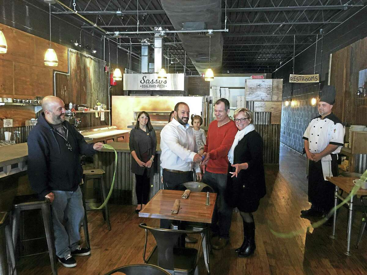 Ben Lambert - The Register Citizen Sasso's Coal Fired Pizza opened in downtown Torrington with a ribbon-cutting ceremony on Friday. Owners cousins Matt Cipriano and Jeff Smart, left and center, were joined by Mayor Elinor Carbone on Friday at the restaurant on Main Street.