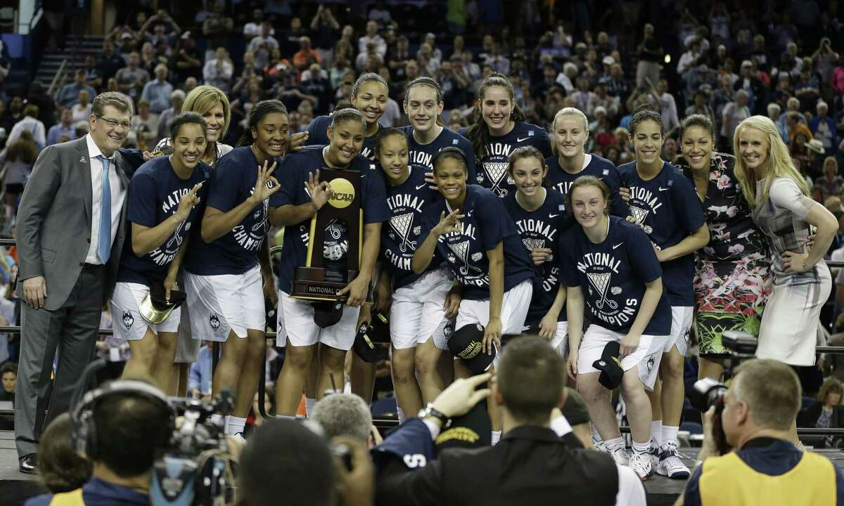 UConn players and coaches pose for photos after winning the national championship against Notre Dame on Tuesday in Tampa, Fla.
