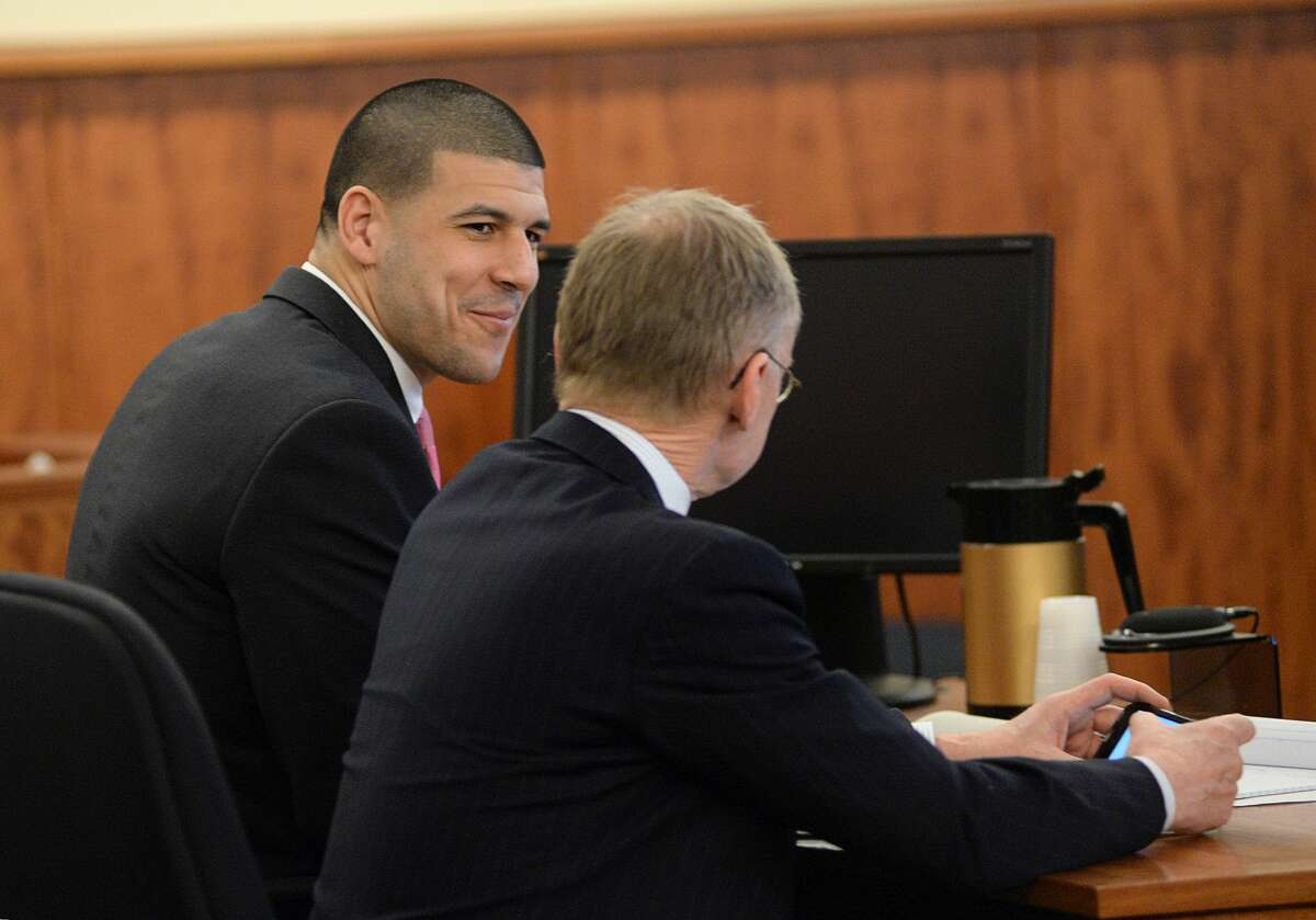Aaron Hernandez smiles with defense attorney Charles Rankin in the courtroom of the Bristol County Superior Court House on Wednesday in Fall River, Mass.