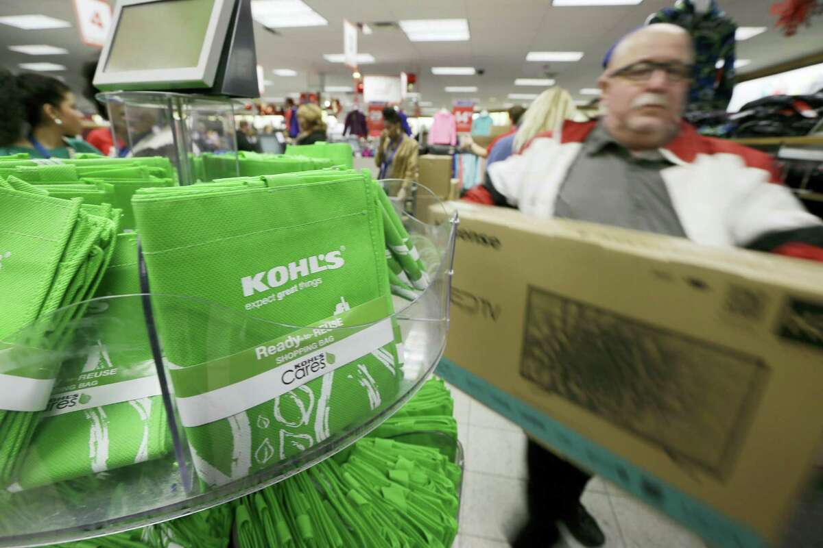 A customer carries a television from the checkout at a Kohl's department store in Sherwood, Ark.