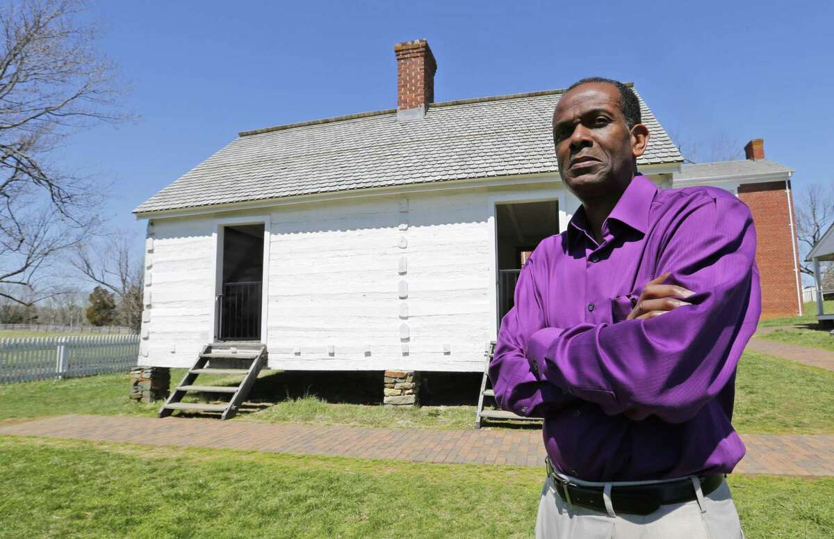 Rev. Alfred L. Jones III poses in front of the reconstructed slave quarters behind the McLean House in Appomattox, Va.