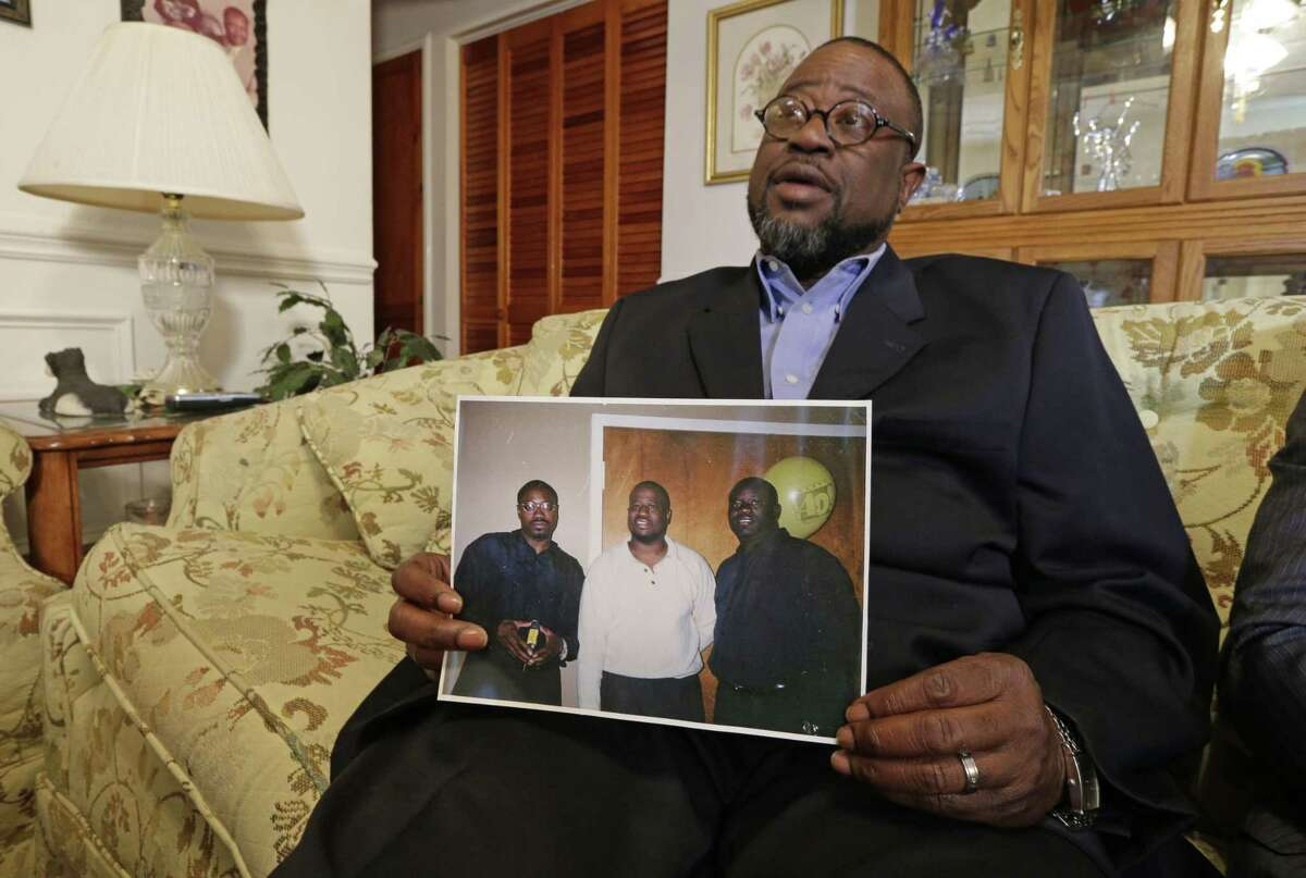 Anthony Scott holds a photo of himself, center, and his brothers Walter Scott, left, and Rodney Scott, right, as he talks about his brother at his home near North Charleston, S.C. on April 8, 2015.