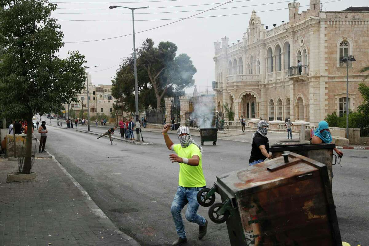 This Friday, Oct. 23, 2015, photograph shows Palestinians clashing with Israeli troops in front of the Intercontinental hotel in the West Bank city of Bethlehem. The century-old Jacir Palace hotel, with its soaring stone archways and wrought iron balconies, was once a symbol of Bethlehem's wealth and tourism potential. Today, the property reflects the city's dour mood ahead of the crucial Christmas season after months of unrest that has taken more than 100 lives, including a Palestinian waiter from the hotel.