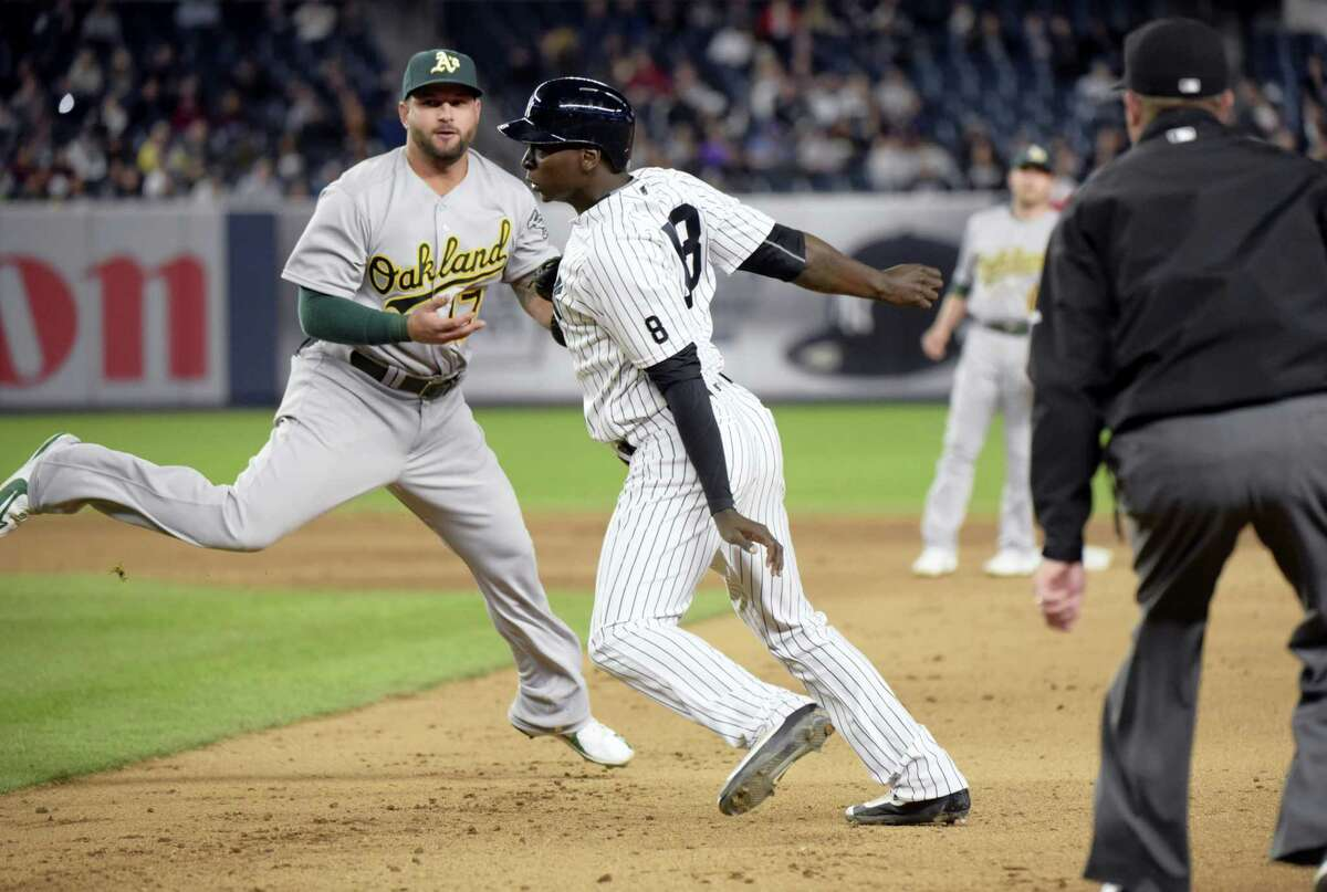 The Yankees' Didi Gregorius is tagged out by Athletics first baseman Yonder Alonso, left, after being caught in a rundown during the fifth inning on Tuesday.
