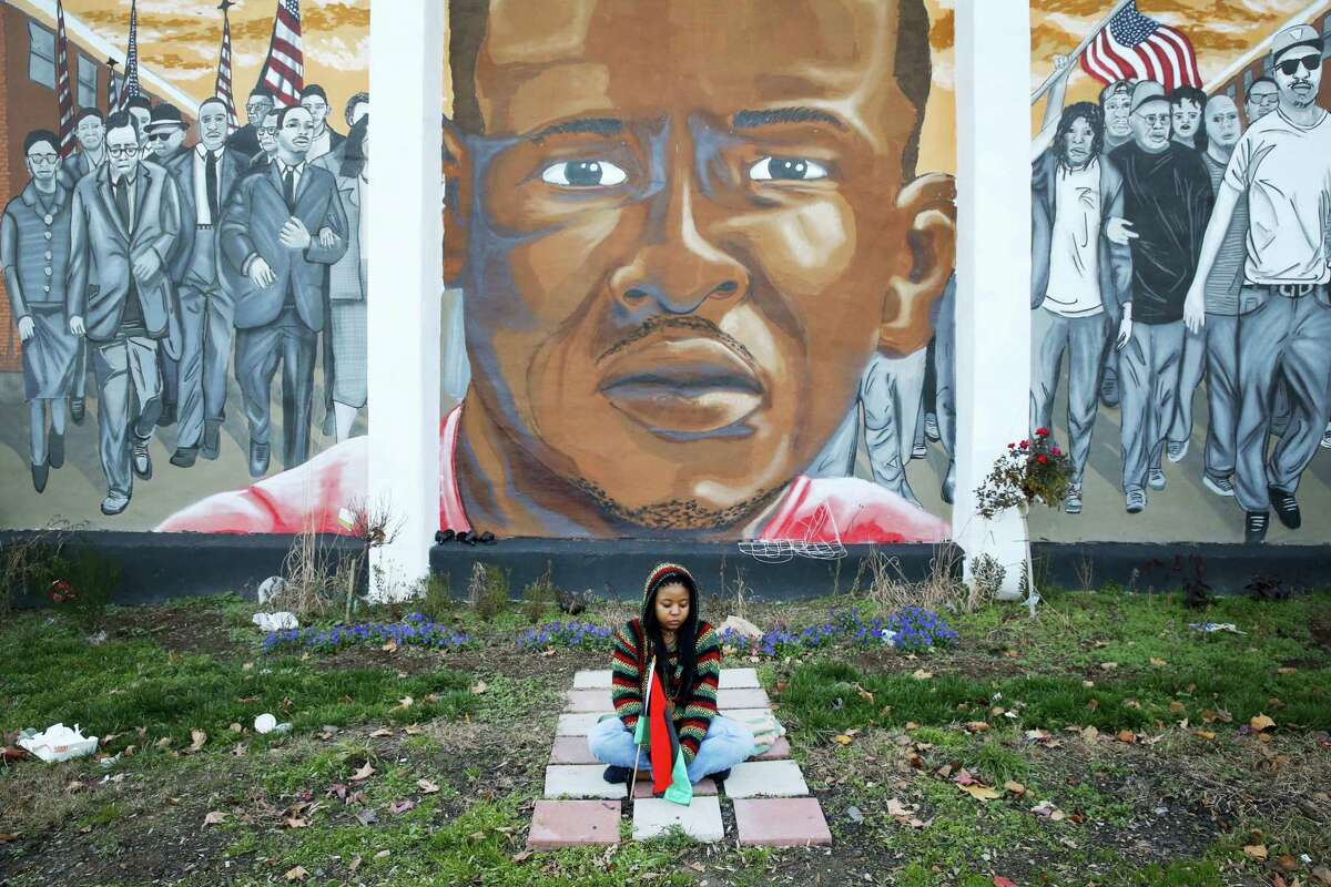 In this Dec. 16, 2015 photo, Jazmin Holloway sits below a mural depicting Freddie Gray at the intersection of his arrest in Baltimore following a hung jury and a mistrial in the trial of police officer William Porter. Gray's death a week after he was injured in a police transport van became a focal point in the national debate over police treatment of African-Americans. When the smoke cleared, Baltimore looked much the same, but change has been gradually cropping up.