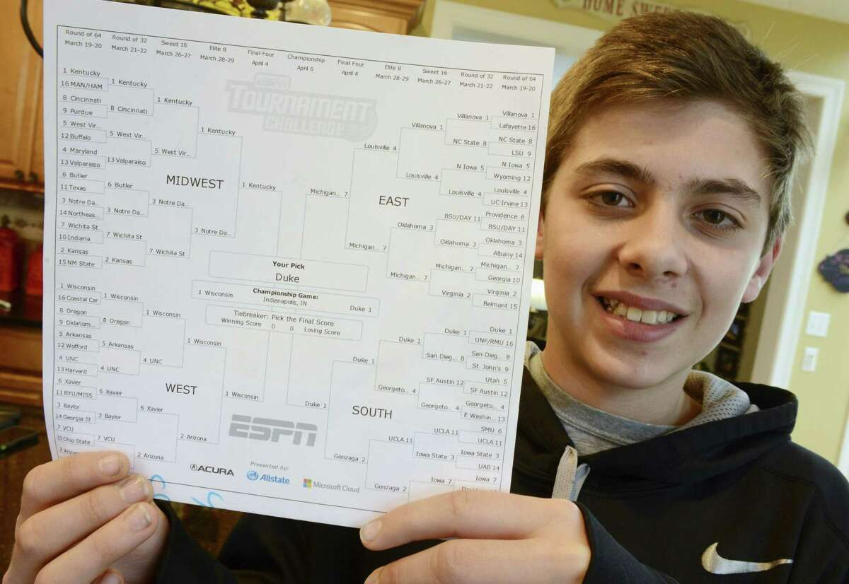Sam Holtz, a sixth-grader from Hawthorn Woods, Ill., poses at home Tuesday with his near-perfect ESPN NCAA men's basketball bracket where he picked Duke to defeat Wisconsin in the final. ESPN officials told Holtz he is ineligible to claim the top prize — a $20,000 gift card — because he's 12 years old.