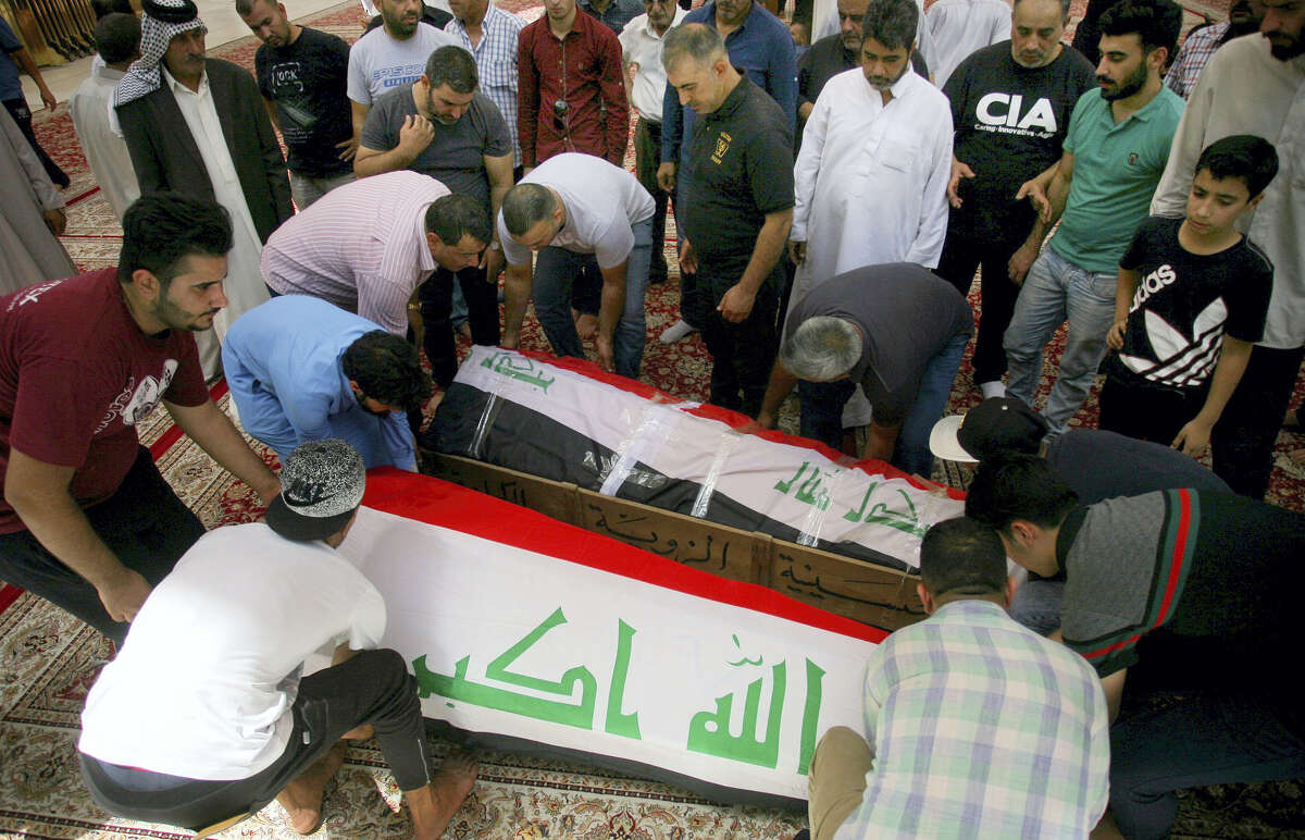 Mourners carry the Iraqi flag-draped coffins of bomb victims, Talib Hassan, 35, and Hamza Jabbar, 37, during their funeral processions at the holy shrine of Imam Ali in Najaf, 100 miles (160 kilometers) south of Baghdad, Iraq on July 3, 2016. Dozens of people have been killed and more than 100 wounded in two separate bomb attacks in the Iraqi capital Sunday morning, Iraqi officials said.