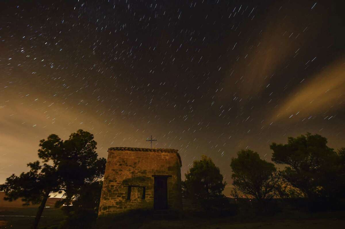Stars seen as streaks from a long camera exposure are seen behind Arnotegui Hermitage, in Obanos, northern Spain, Tuesday, Aug. 11, 2015. The meteor shower is expected to peak Wednesday night into Thursday morning.