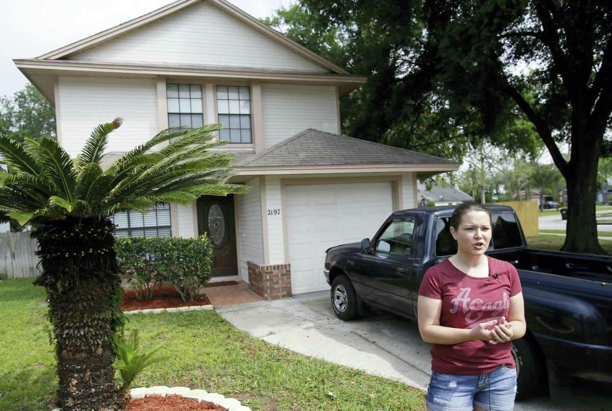 In this April 14, 2016 photo, Nicole Caverly stands in front of her home in the Piedmont Park neighborhood in Apopka, Fla. Caverly began renting in the Piedmont Park neighborhood this year.