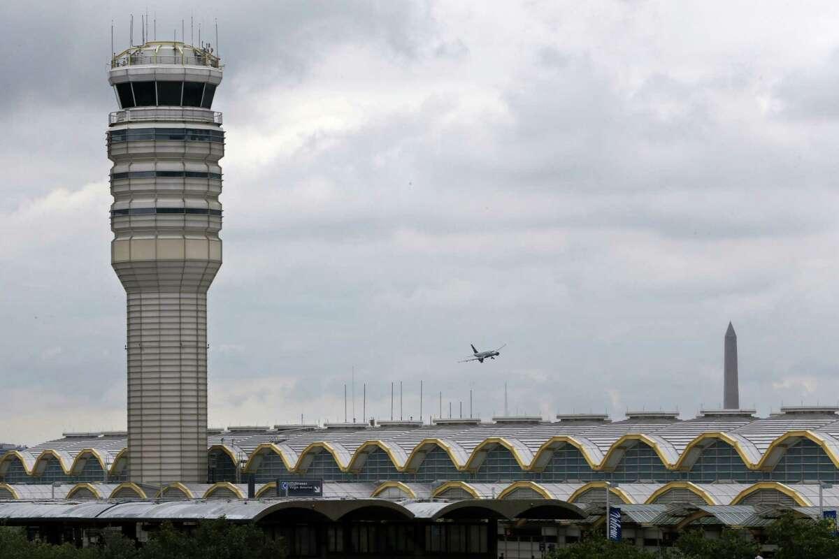 An airplane flies between the air traffic control tower and the Washington Monument at Washington's Ronald Reagan National Airport, Aug. 10, 2015. For more than three years, the government has kept secret a study it requested that found air traffic controllers' work schedules often lead to chronic fatigue, making them less alert and endangering the safety of the national air traffic system, according to report on the study obtained by The Associated Press.