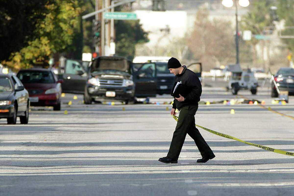 An investigator walks with a yellow tape near a Black SUV that was involved in Wednesday's police shootout with suspects, Thursday, Dec. 3, 2015, in San Bernardino, Calif. A heavily armed man and woman dressed for battle opened fire on a holiday banquet for his co-workers Wednesday, killing multiple people and seriously wounding others in a precision assault, authorities said. Hours later, they died in a shootout with police.