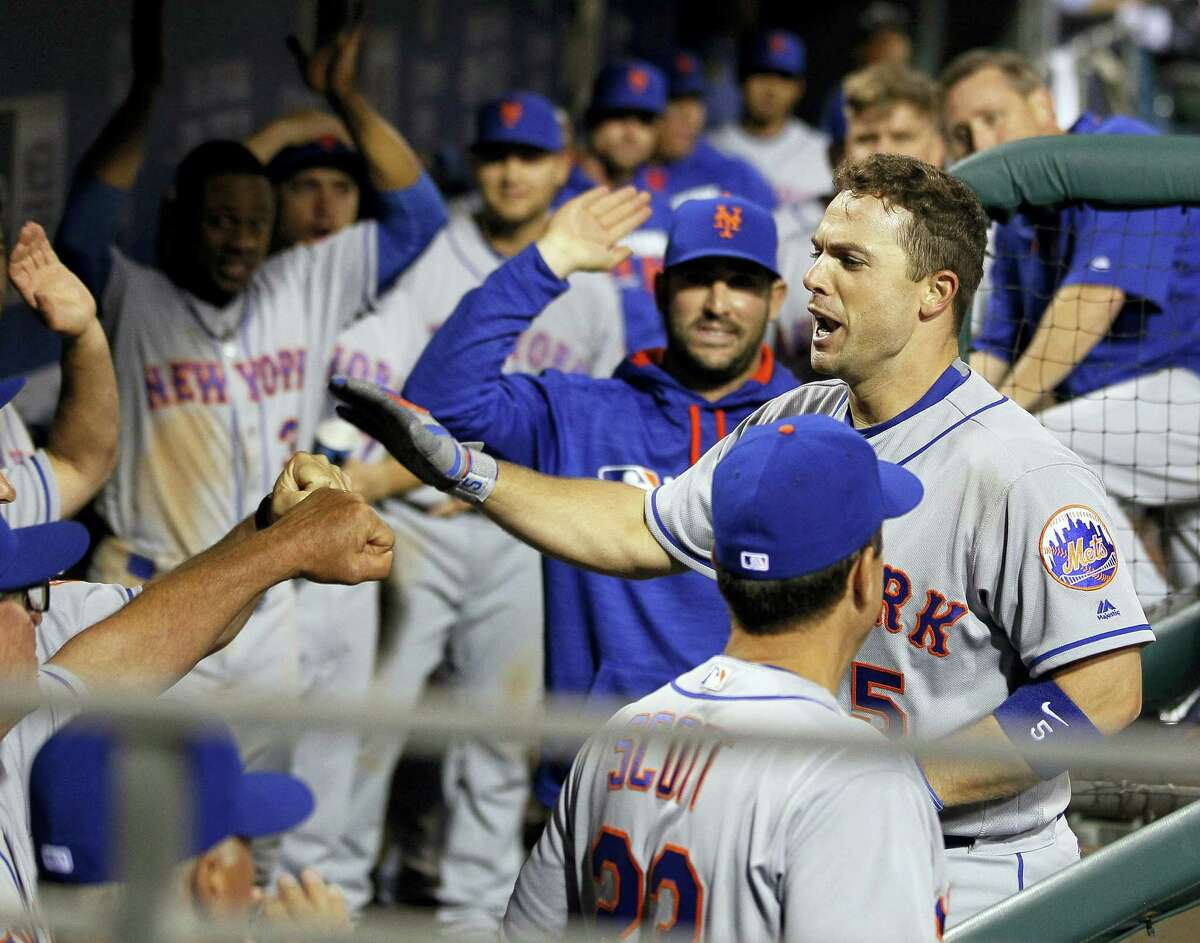 David Wright is greeted in the dugout with high fives after his second homer of the night during the ninth inning of the New York Mets' 5-2 victory over the Philadelphia Phillies on Monday night in Philadelphia.