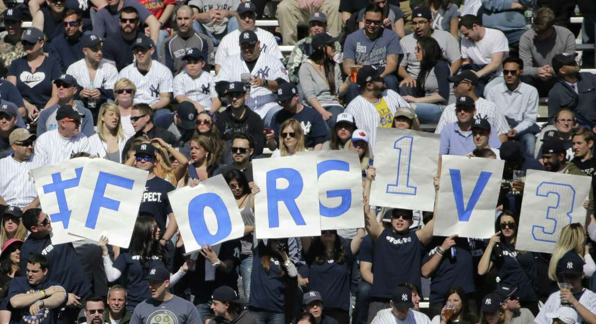 Signs in the stands encourages fans to forgive New York Yankees designated hitter Alex Rodriguez (13) as he batted in the seventh inning of an opening day baseball game against the Toronto Blue Jays in New York, Monday, April 6, 2015. Rodriguez lined out to right field in his final at bat.