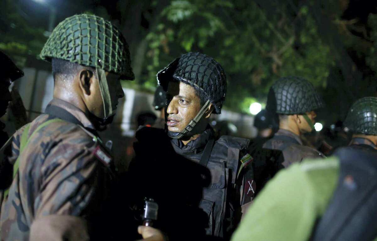 Bangladeshi security personnel stand guard near a restaurant that has reportedly been attacked by unidentified gunmen in Dhaka, Bangladesh, Friday, July 1, 2016. Local media reported that a group of attackers took hostages inside a restaurant frequented by both locals and foreigners in a diplomatic zone in Bangladesh's capital.